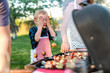 Little chef with apron holding hands on eyes while standing next to grill in backyard. Family gathering concept.