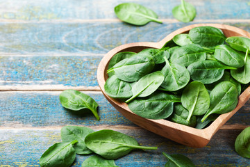 Baby spinach leaves in bowl on wooden table. Organic and healthy food.
