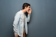 Teenager man with jean jacket over grey wall shouting with mouth wide open to the lateral