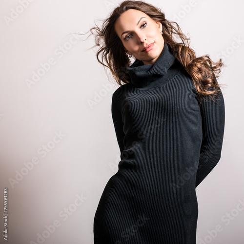 Beautiful girl in stylish black dress posing in studio.