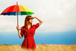 Leinwanddruck Bild - Redhead girl with umbrella at field