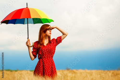 Leinwandbild Motiv Redhead girl with umbrella at field