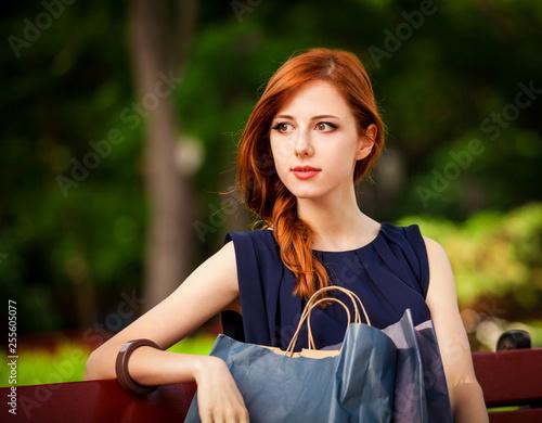fototapeta na ścianę Style redhead women sitting on the bench with shopping bags