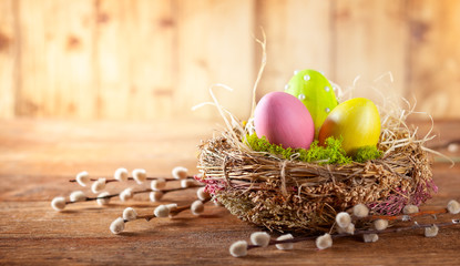 Easter composition with Easter eggs in nest and branches of pussy willows.