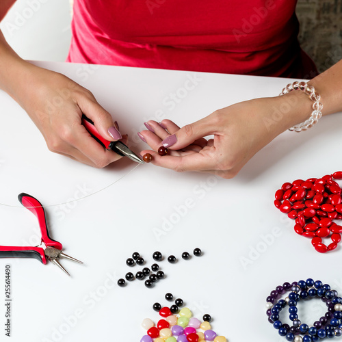 Jewelry making. Female hands with a tool on a white background.
