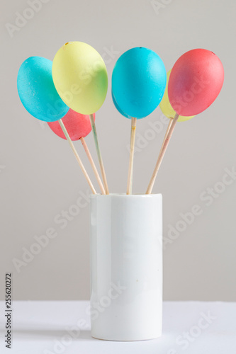 Brightly colored easter eggs in a white vase