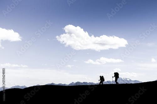 Leinwandbild Motiv Silhouettes of two hikers walking along the cliff edge