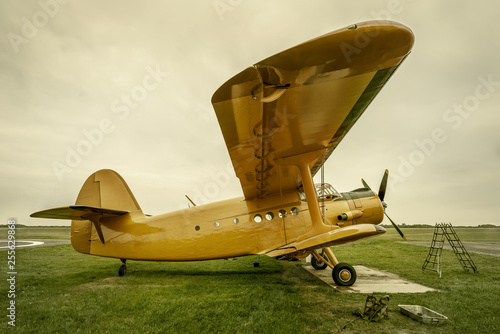 obraz PCV historical airplane gets service on a meadow