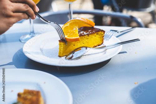 Person eating orange cake