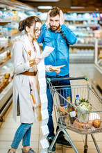 """Постер, картина, фотообои """"Young couple buying food standing with cart and long shopping list in the supermarket"""""""