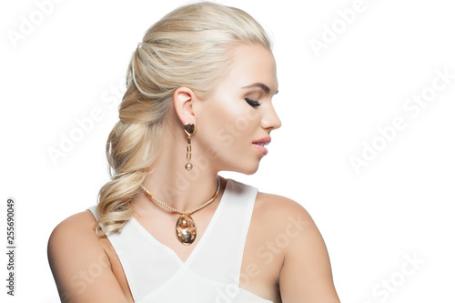 Isolated blonde woman with gold earring and necklace on white background. Beautiful female face, profile © millaf