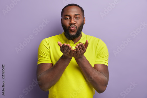 Middle aged dark skinned Afro American man pulls forwards palms, blows air kiss, has love expression, expresses affection to beloved person, wears casual t shirt, isolated over purple background