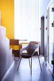 Black chair in the hallway of the apartment, a real photo with a copy of the space on the white wall. Beautiful office space. The interior of the office and premises.