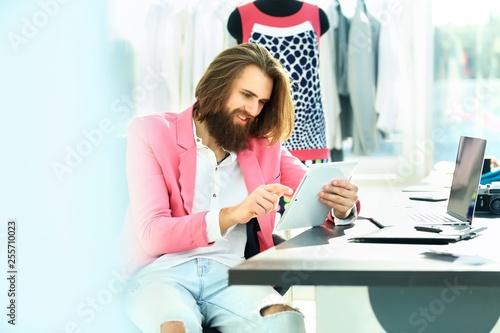 designer uses a digital tablet sitting in his Studio