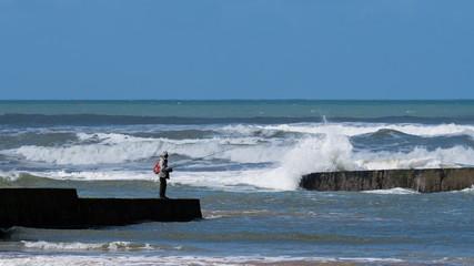 Pêcheur sur une jetée en bord de mer en Vendée © juju