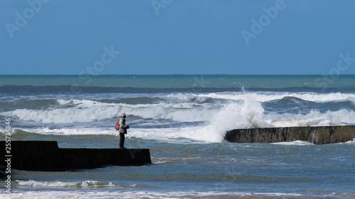 Pêcheur sur une jetée en bord de mer en Vendée - 255736846