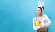 Young woman with an Easter bunny on a blue background