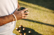 Close up of a man standing in a lawn holding a boules