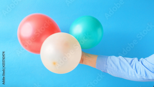 hand holding colored balloons on blue background. Holiday concept