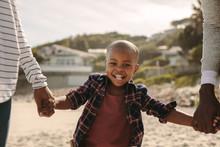"Постер, картина, фотообои ""Smiling boy walking with parents on the beach"""