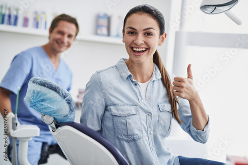 Leinwanddruck Bild Lovely young lady doing thumbs up sign at modern dental office