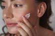 Close up of young sensual woman applying cream