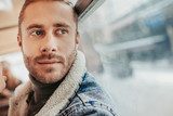 Hipster young male going in bus near window