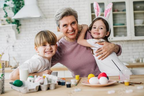 Half length of gray-haired woman hugging her grandchildren in kitchen