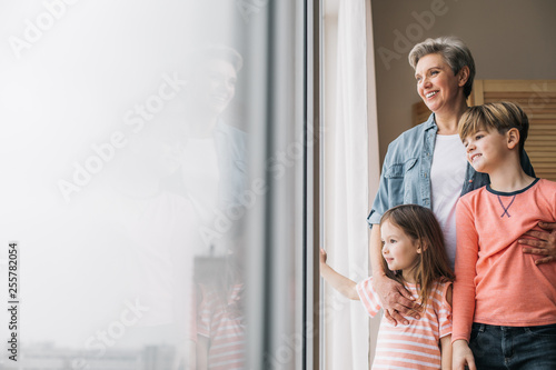Waist up photo of smiling granny and her grandchidren at window