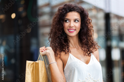Cheerful woman with shopping bag in town