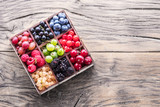 Colorful berries in wooden box on the table. Top view.