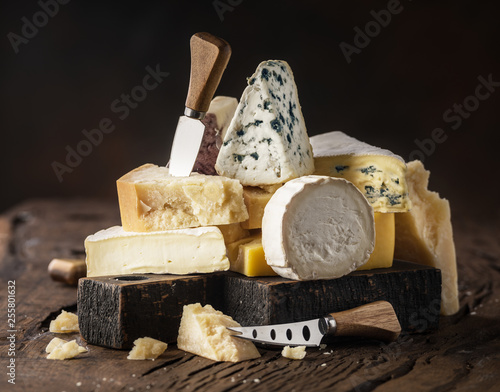 Assortment of different cheese types on wooden background. Cheese background. © volff