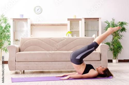 Leinwanddruck Bild Young beautiful girl doing exercises at home