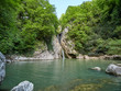 A high waterfall falls from a cliff into a clear lake. The waterfall is surrounded by green forest - 255815284