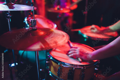 man plays musical percussion instrument with sticks closeup on a black background, a musical concept with the working drum, beautiful lighting on the stage. - 255816440