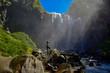 una chica contempla la caida de agua de una cascada - 255830634