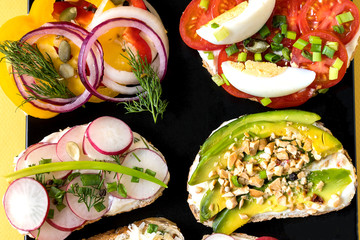 Sandwiches prepared with cream cheese and vegetables, on black plate. Healthy food for lunch or breakfast. Copy space, flat lay.