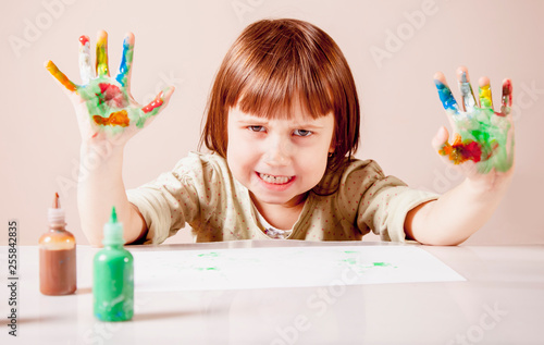 Beautiful little child girl with colorful painted hands. Funny portrait.