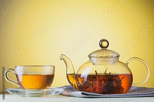 Transparent glass cup and teapot of flower green tea at yellow background © Serhii Moiseiev