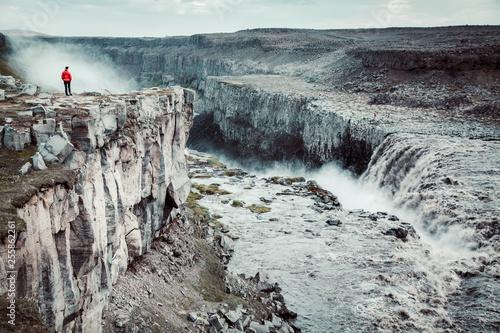 Leinwanddruck Bild Hiker at gigantic Dettifoss waterfall in Iceland