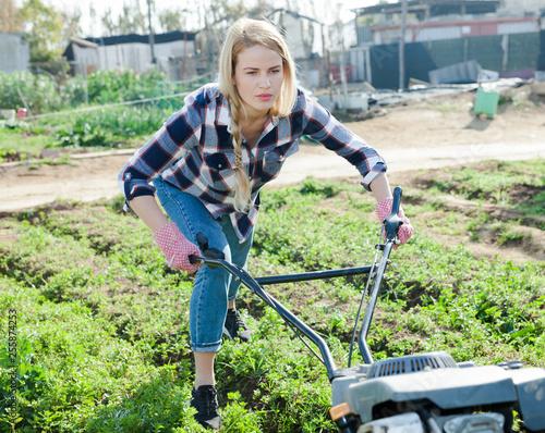 Foto Murales Farmer woman using motorized cultivator in his garden