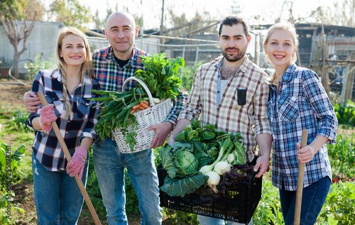 Family of four professional gardeners holding  harvest of vegetables and greens - 255874261