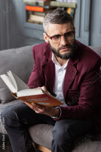Man wearing white shirt and jacket reading book having break from work