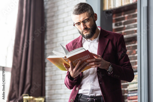 Stylish handsome man standing near window while reading book