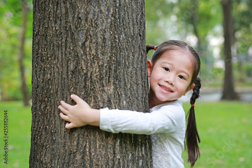 Foto Murales Happy little Asian child girl embracing a big tree in the garden.