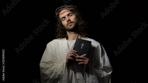 Jesus Christ with closed eyes in crown of thorns holding bible, spirit of god