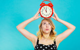 Blonde girl with alarm clock on blue.