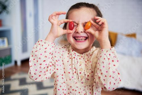 Leinwanddruck Bild Girl holding tomatoes in front of her eyes