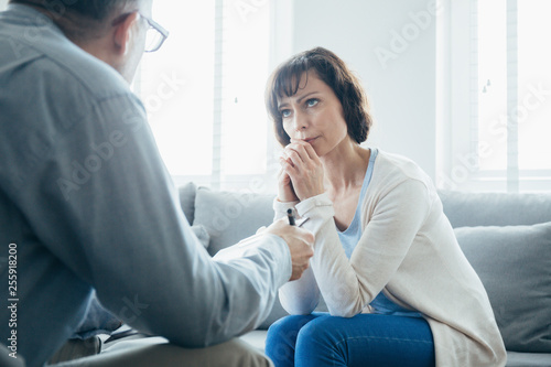 Leinwanddruck Bild Depressed woman searching help at the psychotherapist