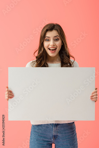 Leinwandbild Motiv happy and beautiful woman holding empty board with copy space isolated on pink